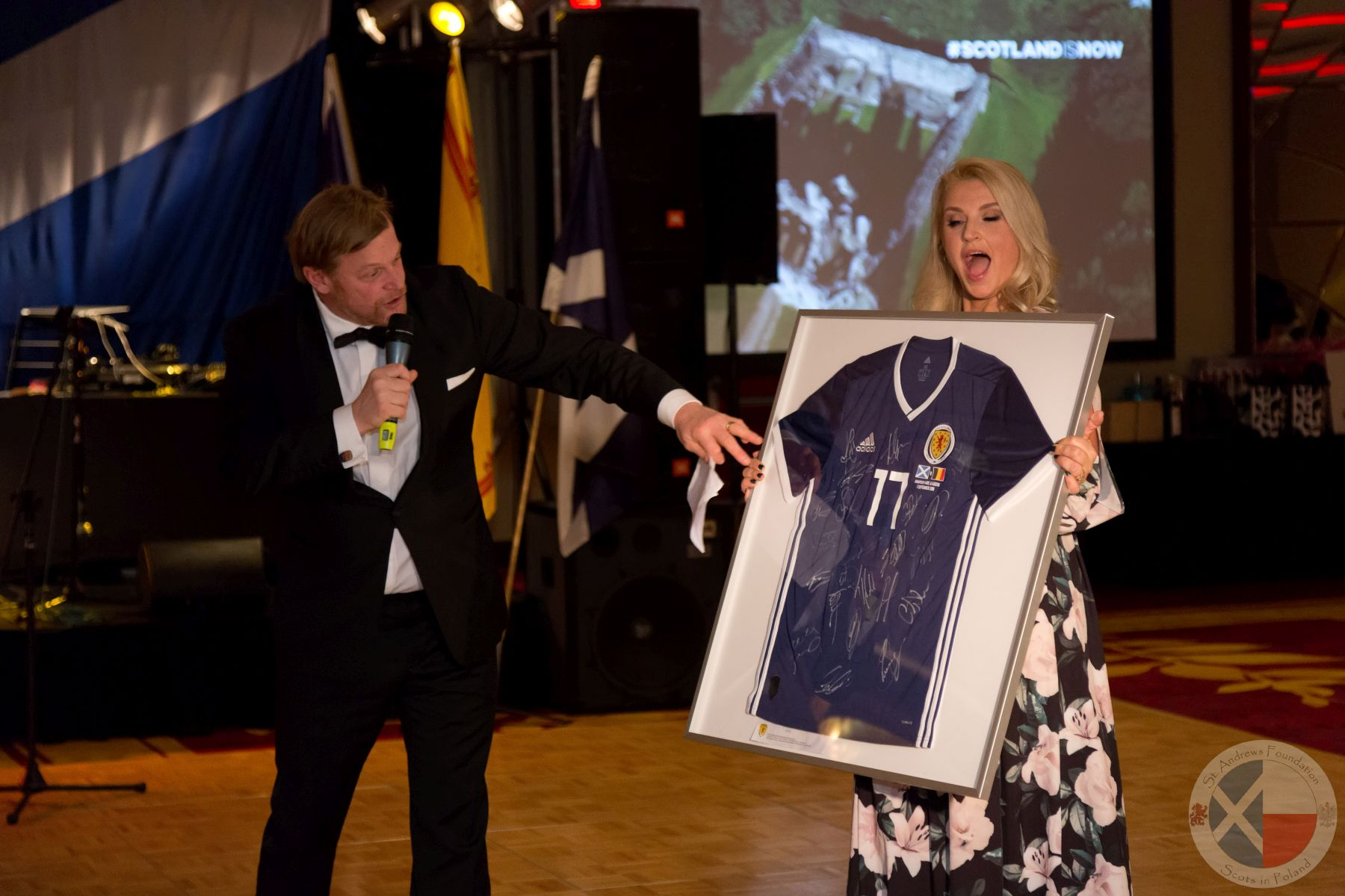Auctioneer Robert Mielżyński auctions a singed Scotland Football shirt